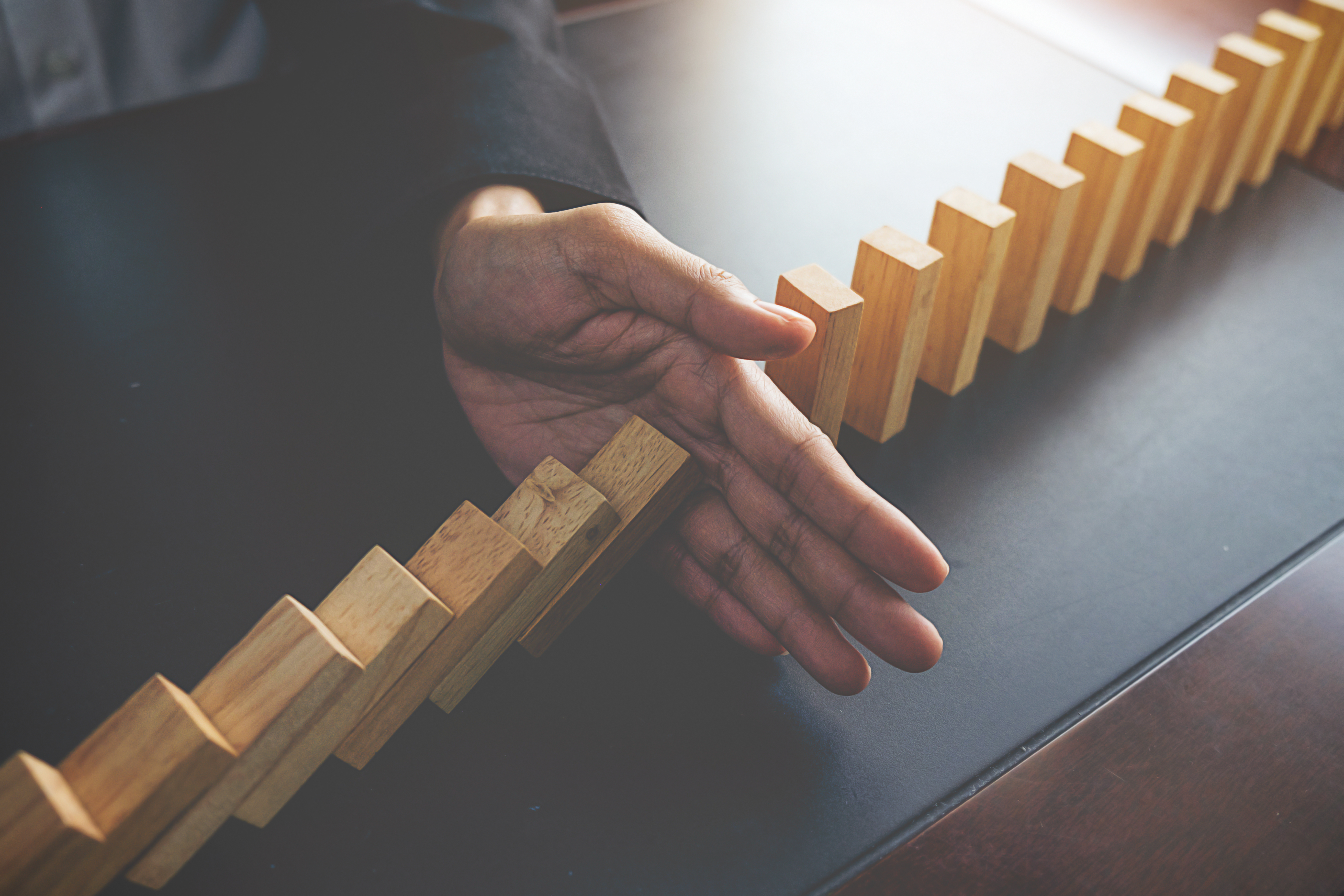 Problem Solving,Close up view on hand of business woman stopping falling blocks on table for concept about taking responsibility.